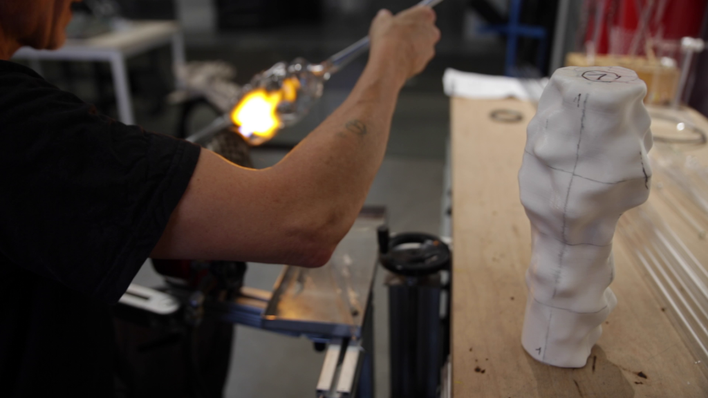 Glass blower at Grand Garage at work following the shape of the 3D printed object (Video Still, Credit: Antoni Rayzhekov)