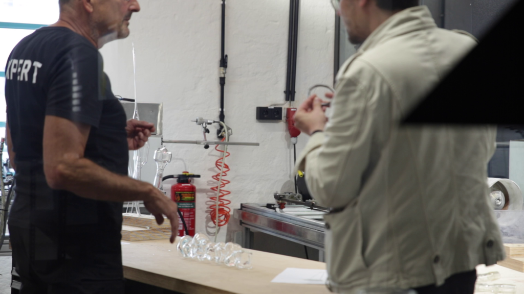 Metal worker at Grand Garage and Antoni Rayzhekov discussing the metal mount of the glass piece on the sculpture (Video Still, Credit: Antoni Rayzhekov)
